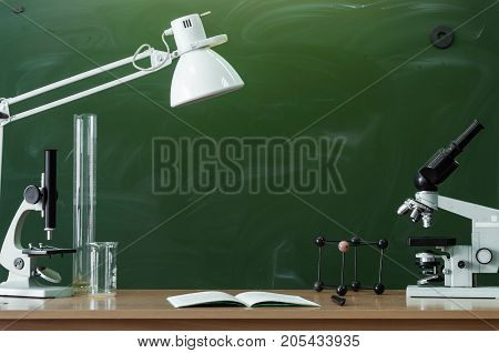 Teacher or student desk table. Education background. Education concept. Microscopes beakers copybook with pen and lamp on the table. Chemistry or biology lesson.