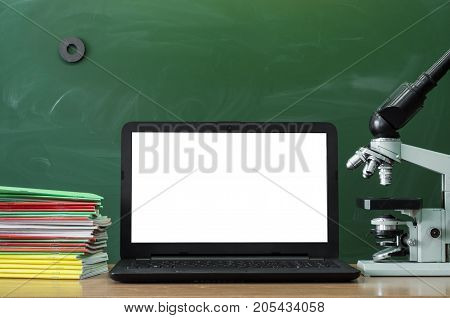 Teacher or student desk table. Education background. Education concept. Laptop with blank screen microscope and stacked books on the table.