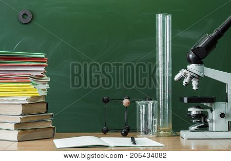 Teacher student biologist or chemist desk table. Education background. Education concept. Microscope vial flask beaker stacked books and copybook book with pen on the table.