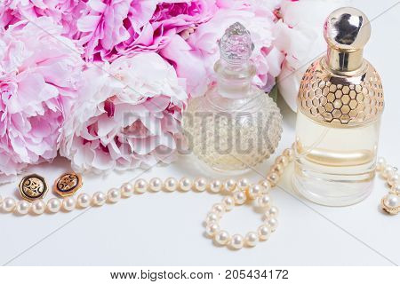 Female lifestyle with fresh pink peony flowers, glamour bottles and jewellery close up