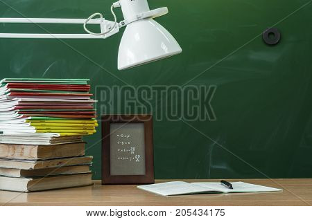 Teacher or student desk table. Education background. Education concept. Stacked books copybook handbook photo frame and lamp on the table.
