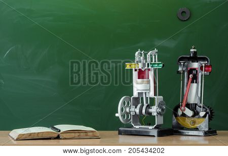 Teacher student or engineer desk table. Education background. Education concept. Open book textbook and education models of internal combustion engine on the table.
