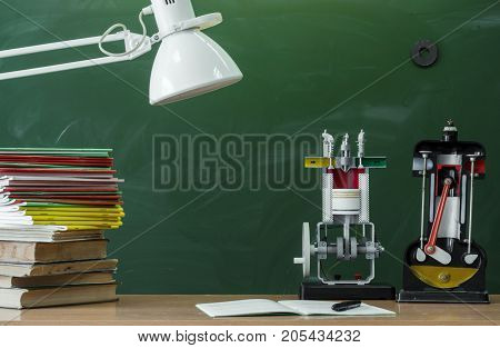 Teacher student or engineer mechanics desk table. Education background. Education concept. Education models of internal combustion engine stacked books copybook and lamp on the table.