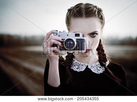Lovely sad young girl photographing on the vintage film camera. Closeup outdoor portrait