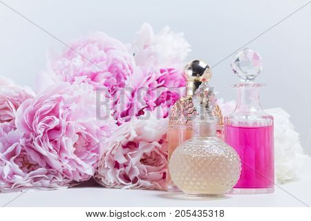 Pink Peony essence oil and water in glass vials and fresh peony flowers