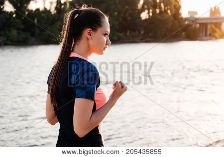 Girl athlete trains and boxing in nature