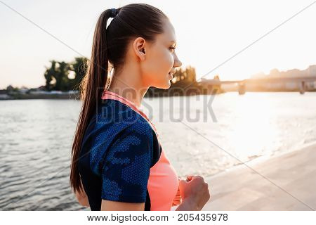 Girl athlete runner at sunset looking into the distance