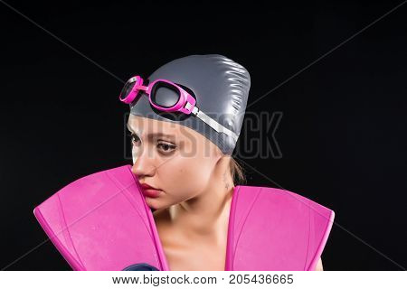 A young woman swimmer holds a thoughtful fins for a swim in her arms