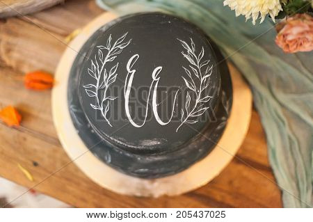 homemade, goodies, present concept. top view on the holidays cake of remarkable black colour, it has white painted brunch with leaves and initials