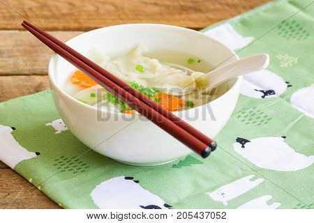 Homemade minced pork wonton soup in white bowl on napkin put on wood table. Delicious wonton in clear soup for breakfast or lunch or dinner. Wonton or dumpling is always popular Chinese food. Dumpling wonton soup ready to served.