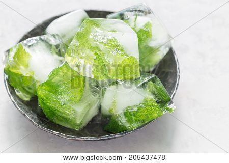 Homemade ice cubes with mint leaves inside on a metal plate ice for lemonade and cocktail horizontal copy space