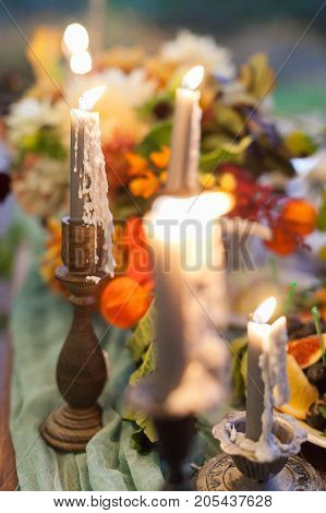 illumination, comfort, decoration concept. in the original and shapely wooden holders that are standing among the flowers there are tall burning candles that have colour of light grey smoke