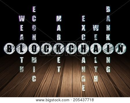 Money concept: Glowing word Blockchain in solving Crossword Puzzle in grunge dark room with Wooden Floor, black background