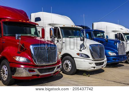 Indianapolis - Circa September 2017: Colorful Red White and Blue Semi Tractor Trailer Trucks Lined up for Sale XVIII