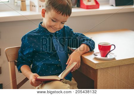 Boy reading a book sitting on a chair near a table with a cup of tea. Education, Knowledge, getting ready for school.