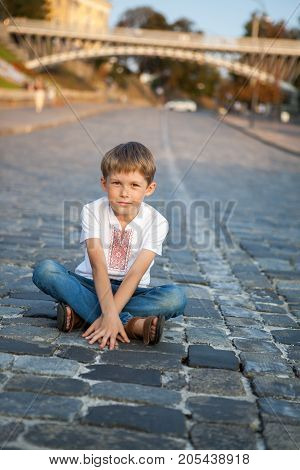 The boy is sitting on the road. little boy squints sitting on the road. He smiles.