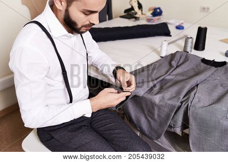 Talented bearded tailor sitting at working table and sewing custom-made male jacket by hands, interior of modern studio on background