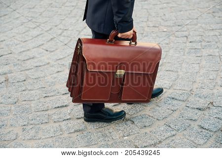 Close up shot of future businessman holding leather briefcase while walking on pavage street outdoor in city. Braun leather bag with golden belt on gray stone background. Copy space available.