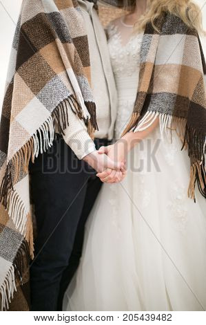 love, engagement, atmosphere concept. there is a sweet couple of newlyweds dressed in wedding costumes and wrapped up in cosy plaid with fringe, they are holding hands of each other