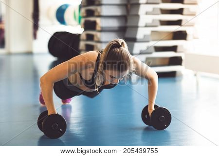 Young Strong Girl Doing Push-ups On Dumbbells In The Gym