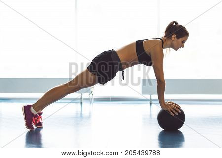 Young Strong Girl Doing Plank With The Ball In The Gym.