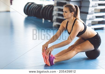 Young Strong Girl Doing Stratching With The Ball In The Gym.