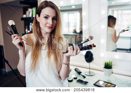 Pretty smiling woman standing with a variety of make-up brushes at beauty studio.