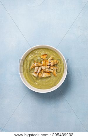 green soup puree with croutons in a white bowl on a blue background. view from above