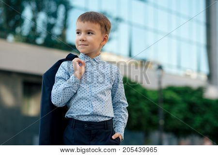 Portrait elegant little man in fashionable navy blue shirt holding dark blue jacket on his back smiling and looking to camera on urban background. Young boy posing. Boy ready for school.