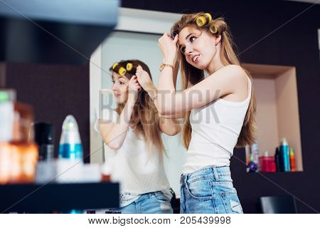Teenager girls applying hair rollers on their long blond hair preparing to go out.