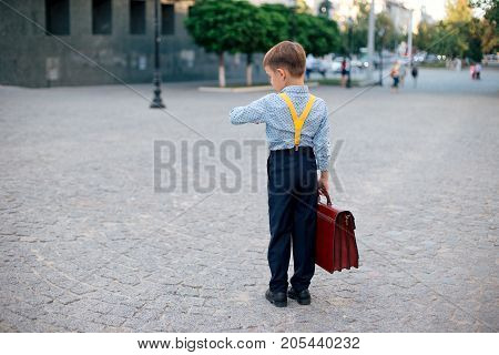 Concept future businessman. Back view boy in dark blue pants, baby blue shirt and yellow straps, standing on pedestrian street with braun briefcase looking to his watch, urban background.