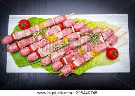 Group Of Meat Skewers On Black Wood Table