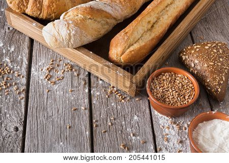 Fresh white and rye background. Homemade baguette loaves on wooden tray, rye bun, grain and flour in clay bowls and on rustic table, copy space