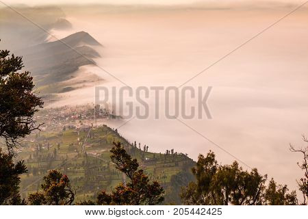 Landscape of Cliff and Cemoro Lawang village in high angle view with sea mist at Mount Bromo volcano in Bromo tengger semeru national park, East Java, Indonesia