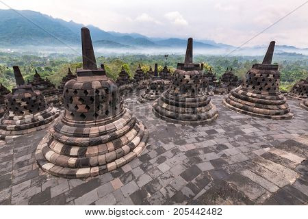 Borobudur buddhist temple with mountain and fog in the morning day in Yogyakarta Java Indonesia. (UNESCO World Heritage Site)