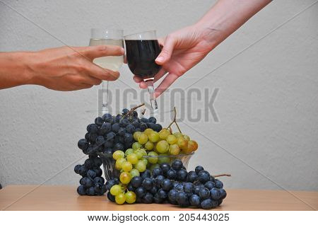 Hands toasting wine glasses in front of grape. Toasting wine in front of fruit