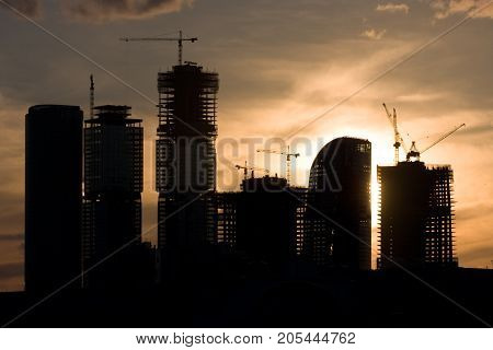 Construction of skyscrapers of the business center of Moscow City at sunset. Silhouettes of buildings against the backdrop of the setting sun