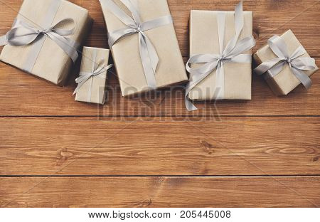 Presents for any holiday concept. Gift boxes frame, top view with copy space on wood table background. Border of gold packages with silver satin ribbons for christmas, valentine day or birthday