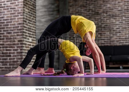 Young sporty mother and little girl doing stretching gymnastic exercises together standing in crab posture on mat in loft studio.