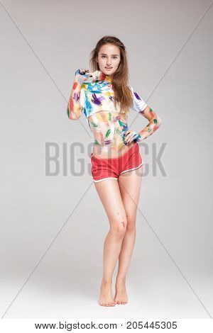 young woman with paint brush is dirty in multicolored paint. girl is fooling around