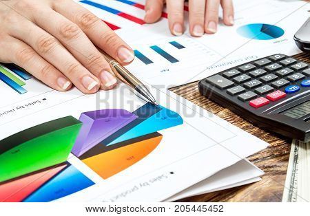 Businesswoman's hand holding pen and pointing on business graph. Explaining data information of business results. Financial concept.