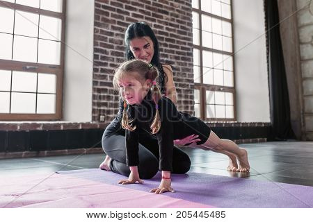 Smiling children gym trainer working with a little girl showing how to do plank exercise in fitness studio.