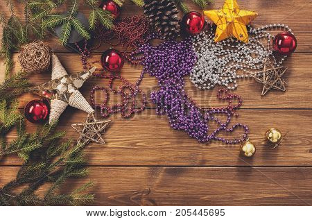 Prepare for christmas eve or other winter holidays. Xmas decorations, fir tree and garlands concept background, top view on wood with copy space. Ornaments, tinsel, stars, spruce branch and balls
