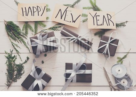 Winter holidays celebrating. Gift wrapping and decorating. Packaging modern hew year present boxes in paper with satin silver ribbon. Top view of text on white wood table with fir tree branches.