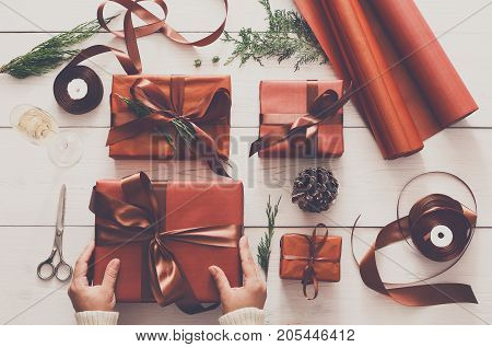 Christmas eve, preapring for holidays. Gift wrapping. Packaging stylish present boxes in maroon paper decorated with satin ribbon bows. Winter holidays concept, top view, flat lay