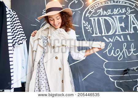 Portrait of happy young woman trying on new clothes in store, holding autumn trench coat and hat