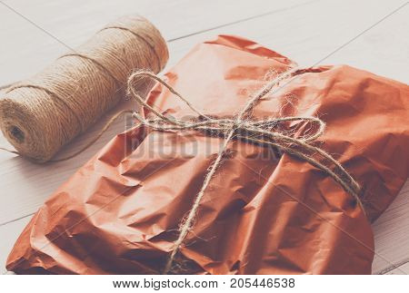 Gift wrapping background. Packaging sweater as christmas present in maroon paper decorated with twine rope on white wood table. Winter holidays concept.