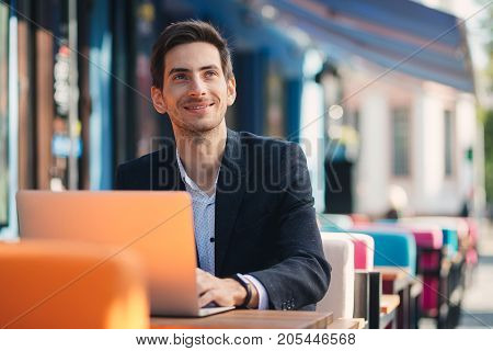 Smiling modern entrepreneur working on laptop sitting at table in colorful cafe. Ambitious freelancer, dressed in casual black jacket and unbuttoned shirt typing while thinking about future results.