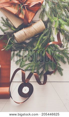 Gift wrapping background. Rope for packaging stylish christmas present boxes in maroon paper decorated with satin ribbon. Christmas and winter holidays concept. Still life, vertical image