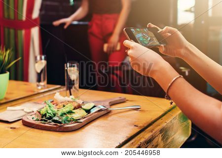 Close-up image of female hands holding a mobile phone taking picture of healthy delicious dish in cafe.